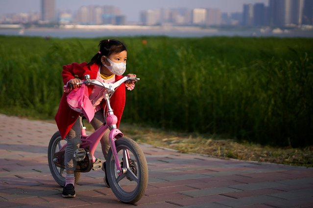 A girl wearing a face mask rides her bicycle at a park after the lockdown was lifted in Wuhan, capital of Hubei province and China's epicentre of the novel coronavirus disease (COVID-19) outbreak, April 12, 2020. (Photo by Aly Song/Reuters)
