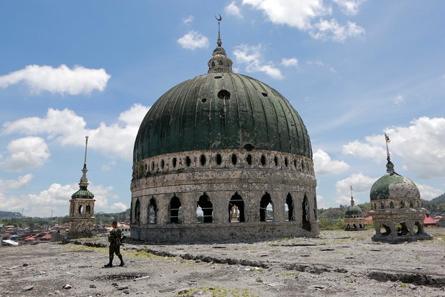 A soldier from the Armed Forces of the Philippines walks past a destroyed mosque in the war-torn Marawi City, the Philippines, May 22, 2018. The rehabilitation work in the former battle area in the war-torn Marawi city will start in June and will be completed by 2021, a Philippines official said on Monday. (Photo by Xinhua News Agency/Rex Features/Shutterstock)