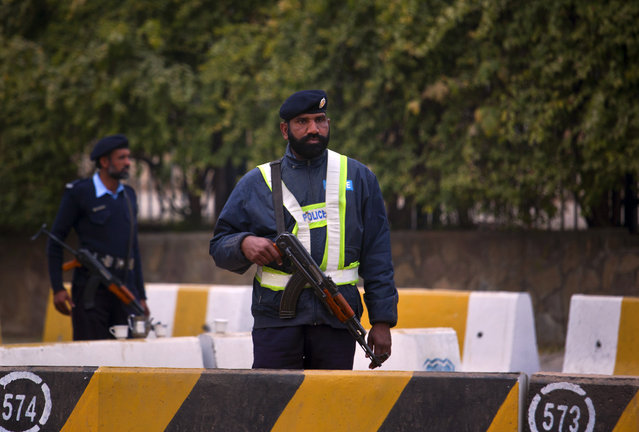 Pakistani police officers stand guard at an entry point of the parliament building in Islamabad, Pakistan, Monday, January 5, 2014. Pakistani lawmakers have opened debate in parliament on a constitutional amendment tabled by the government to form special military courts for trial of terrorists. (Photo by Anjum Naveed/AP Photo)