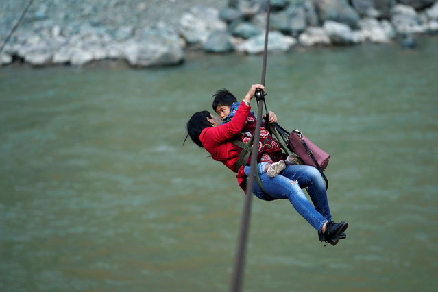 Cha Huilan, a 40-year old Lisu woman, and her daughter leave Lazimi village with a zipline across the Nu River in Nujiang Lisu Autonomous Prefecture in Yunnan province, China, March 24, 2018. (Photo by Aly Song/Reuters)