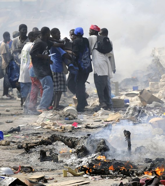 Haitians burn bodies and take goods from stores in the market place as Haitian police try to control the chaos on January 17, 2010 in Port au Prince, Haiti. (Photo by Carol Guzy/The Washington Post via Getty Images)