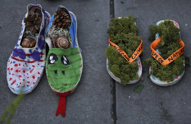 A pair of beach sandals with green moss (R) and French espadrilles with pine cones and snails are symbolically placed on the Place de la Republique, after the cancellation of a planned climate march following shootings in the French capital, ahead of the World Climate Change Conference 2015 (COP21), in Paris, France, November 29, 2015. (Photo by Eric Gaillard/Reuters)