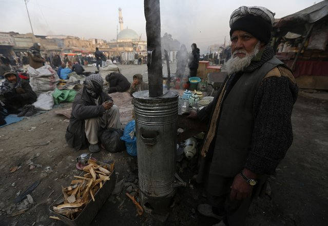 An Afghan man prepares tea for customers at a roadside tea shop during the early morning hours in Kabul, January 11, 2015. (Photo by Omar Sobhani/Reuters)