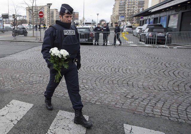 A French police officer prepares to place flowers outside the Hyper Cacher kosher supermarket near Porte de Vincennes in eastern Paris, January 10, 2015. French President Francois Hollande confirmed reports on Friday that four hostages, along with the gunman Amedy Coulibay, were killed at a siege of the Hyper Cacher supermarket in eastern Paris. (Photo by Yves Herman/Reuters)