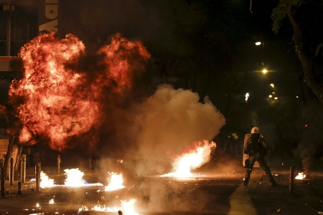 A petrol bomb explodes next to a riot police officer during clashes with hooded youth following an anniversary rally marking the 2008 police shooting of 15-year-old student, Alexandros Grigoropoulos, in Athens, Greece, December 6, 2015. (Photo by Alkis Konstantinidis/Reuters)