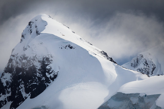 """Summit Attempt"". Mountain climbers in Antarctica struggle near the summit in overcast and threatening storm conditions. (Photo and caption by Joshua Holko/National Geographic Traveler Photo Contest)"