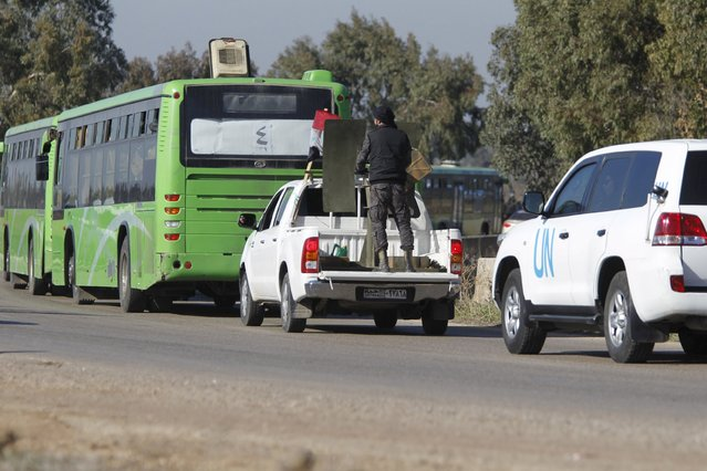 A United Nations vehicle and Syrian Army forces (C) escort buses carrying rebel fighters as they leave the district of Waer during a truce between the government and rebel fighters, in Homs, Syria December 9, 2015. (Photo by Omar Sanadiki/Reuters)