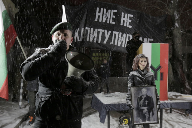 A far-right Bulgarian nationalist speaks on a megaphone during a gathering, in the country's capital, to honour a World War II general known for his anti-Semitic and pro-Nazi activities, in Sofia, Saturday, February 13, 2021. Braving sub-zero temperatures, hundreds of dark-clad supporters of the Bulgarian National Union group flocked to a central square where they had planned to kick off the annual Lukov March, a torch-lit procession held every February to the former house of Gen. Hristo Lukov. (Photo by Valentina Petrova/AP Photo)