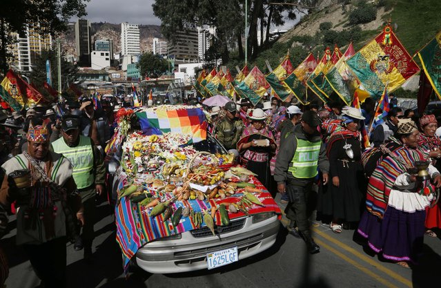 "Hundreds accompany the Bolivian deity statuette ""illa of Ekeko"" as it is driven to the Alasitas Fair, in which Ekeko is the central figure, in La Paz, Bolivia, Saturday, January 24, 2015. The pre-Columbian figurine that symbolizes abundance was recently returned to Bolivia by the National Museum of Berna in Switzerland, 156 years after being taken away from its native country. (Photo by Juan Karita/AP Photo)"