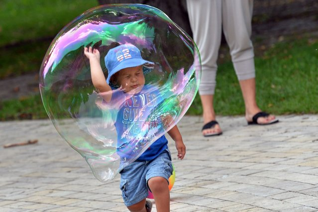 A boy plays with a soap bubble in one of Kiev parks on a hot day in the Ukrainian capital, on July 6, 2013. (Photo by Sergei Supinsky/AFP Photo)