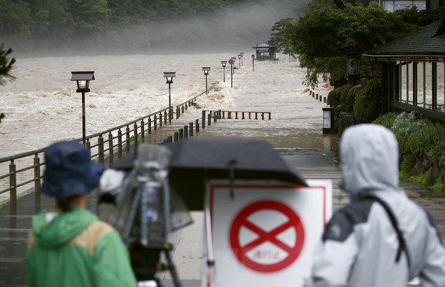 Katsura river is seen swollen due to a heavy rain in Kyoto, western Japan Friday, July 6, 2018. (Photo by Yosuke Mizuno/Kyodo News via AP Photo)