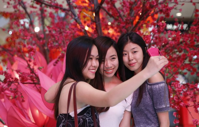 Women take a selfie in front of Chinese New Year decorations in one of Kuala Lumpur's largest shopping malls January 28, 2015. The Chinese Lunar New Year is celebrated on February 19. (Photo by Olivia Harris/Reuters)
