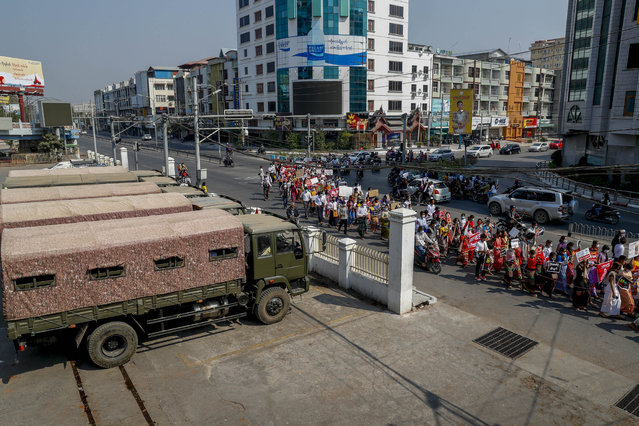 Demonstrators against the recent military coup march past a row of military vehicles in Mandalay, Myanmar, Friday, February 12, 2021. (Photo by AP Photo/Stringer)