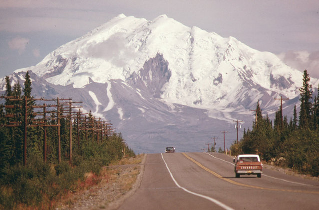 Looking east along Alaska's Glen Highway, toward Mount Drum (Elevation 12,002 Feet) at the intersection of the highway and the under-construction Trans-Alaska Pipeline in August 1974. The 48-inch diameter pipeline will cross the roadway between the two vehicles. The exact point is marked by a pair of wooden stakes along the right shoulder at Mile 673. (Photo by Dennis Cowals/National Archives and Records Administration via The Atlantic)