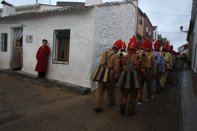 """Women watch as believers parade around town during the """"Endiablada"""" festival in Almonacid del Marquesado, in central Spain February 3, 2015. (Photo by Susana Vera/Reuters)"""