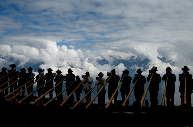 Alphorn blowers perform an ensemble piece on the last day of the Alphorn International Festival on the alp of Tracouet in Nendaz, southern Switzerland, July 22, 2018. (Photo by Denis Balibouse/Reuters)