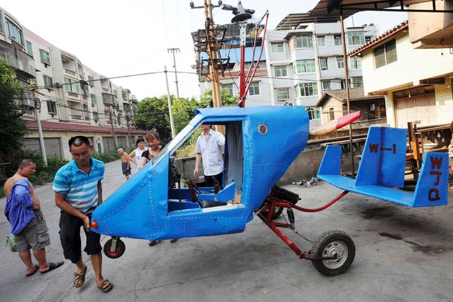 Wen Jiaquan, a 54-year-old motorcycle mechanic, moves his self-made helicopter in Qingping township of Chongqing municipality, China, on July 29, 2013. Wen and his family spent more than three months to build the helicopter using motorcycle components and a used car engine. (Photo by Reuters)