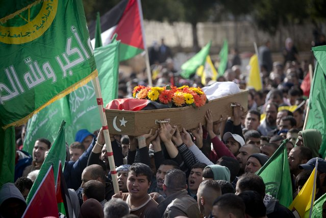 Palestinians mourners carry the body of Mahdia Hammad, 38, during her funeral in the village of Silwad, near the West Bank city of Ramallah, Saturday, December 26, 2015. Hammad was shot and killed Friday when she sped toward Israeli forces, police spokeswoman said. (Photo by Majdi Mohammed/AP Photo)