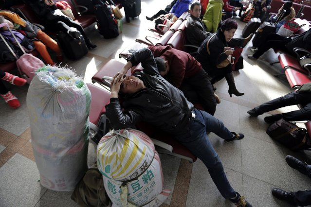 A passenger takes a nap in a waiting room at Beijing Railway Station, February 4, 2015. (Photo by Jason Lee/Reuters)