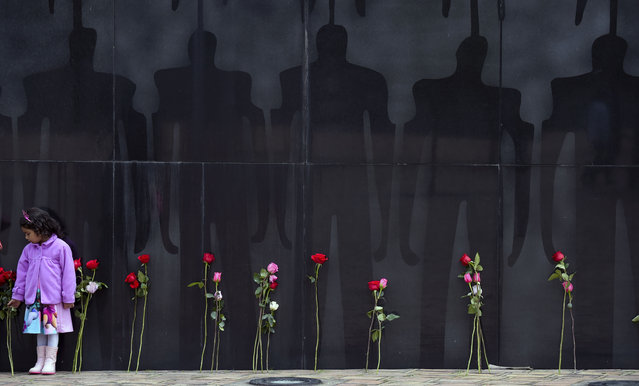 """A girl is pictured during the commemoration of the """"Day of the National heroes and their families"""" in Bogota on July 19, 2018. Every July 19 those that have fallen in combat and their relatives are honoured with a ceremony. (Photo by Raul Arboleda/AFP Photo)"""