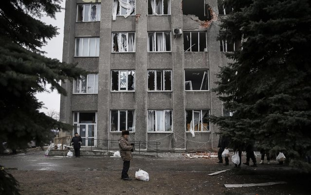 Local residents with bags containing humanitarian aid are seen in front of a delivery point in the Ukrainian forces-controlled town of Debaltseve, eastern Ukraine, February 6, 2015. Convoys of buses converged from two sides on the town of Debaltseve in eastern Ukraine on Friday after separatist rebels and government forces appeared to have patched together a truce to allow civilians to be evacuated. (Photo by Gleb Garanich/Reuters)
