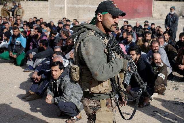 Men sit on the ground as an Iraqi Special forces intelligence team check their ID cards as they search for Islamic State fighters in Mosul, Iraq November 27, 2016. (Photo by Goran Tomasevic/Reuters)
