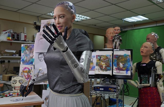 Sophia uses a brush to paint at Hanson Robotics studio in Hong Kong on March 29, 2021. (Photo by Vincent Yu/AP Photo)