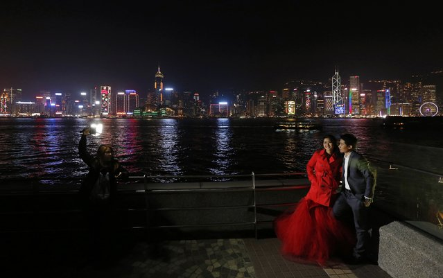 A wedding couple from Thailand poses in front of the skyline of Hong Kong island, featuring Chinese New Year decorations on the facades of commercial towers in Hong Kong February 12, 2015. The Chinese Lunar New Year on February 19 will welcome the Year of the Sheep (also known as the Year of the Goat or Ram). (Photo by Bobby Yip/Reuters)
