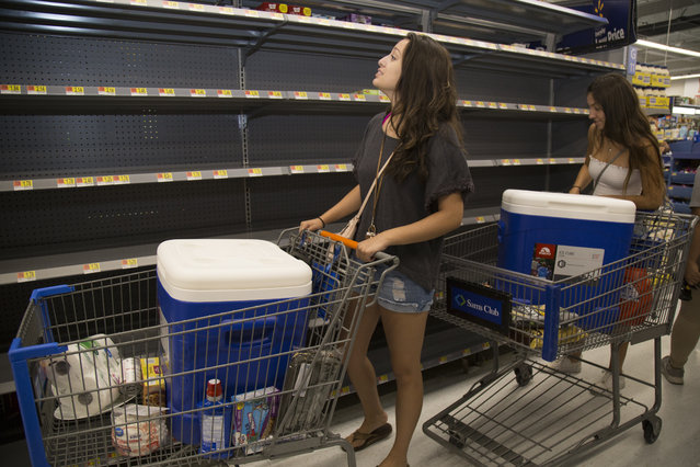 University of Hawaii at Manoa students, Madison Flores, 19, and Loreal Walls-Jaime, who bought coolers in hopes of saving the food in their refrigerator at home if the electricity goes out, look over the empty shelves of can goods at Walmart while in preparation for Hurricane Lane on Wednesday, August 22, 2018 in Honolulu, Hi. Lane is a high-end Category 4 hurricane and remains a threat to the entire island chain. (Photo by Kat Wade/Getty Images)