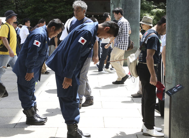 Visitors bow before entering the main gate at Yasukuni Shrine in Tokyo, Wednesday, August 15, 2018. Japan marked the 73rd anniversary of the end of World War II. (Photo by Koji Sasahara/AP Photo)