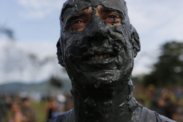"A mud covered reveler poses for the picture during the traditional ""Bloco da Lama"" or ""Mud Block"" carnival party, in Paraty, Brazil, Saturday, February 14, 2015. (Photo by Leo Correa/AP Photo)"