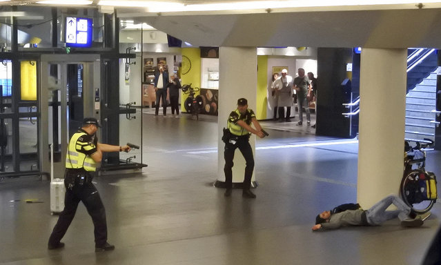 Dutch police officers point their guns at a wounded 19-year-old man who was shot by police after stabbing two people in the central railway station in Amsterdam, the Netherlands, Friday August 31, 2018. Police investigators in Amsterdam included an extremist attack as a possible motive for the stabbings of two people at a busy railway station Friday as authorities in the Dutch capital reported that the suspect shot by police is an Afghan citizen. (Photo by AP Photo/Stringer)