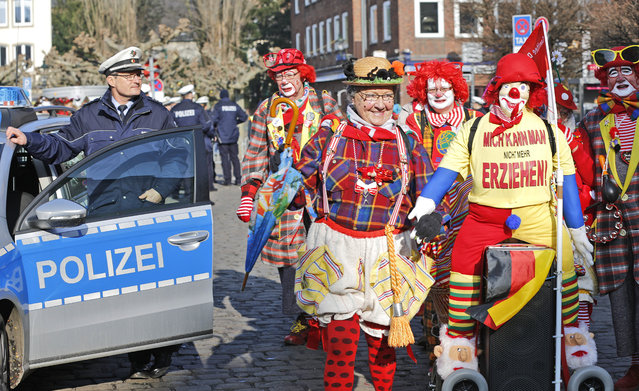 "Revellers pass a police car prior to the traditional Rose Monday carnival parade in Duesseldorf, Germany, Monday, February 16, 2015. Words on the costume at right read: ""I am not educable"". (Photo by Frank Augstein/AP Photo)"
