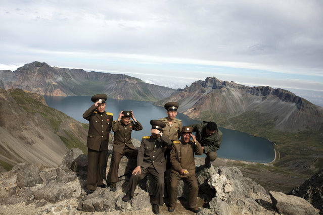 In this photo taken Saturday, August 18, 2018, North Korean soldiers adjust their hats before posing for a photo on a viewing platform overlooking the caldera of Mount Paektu in North Korea. (Photo by Ng Han Guan/AP Photo)