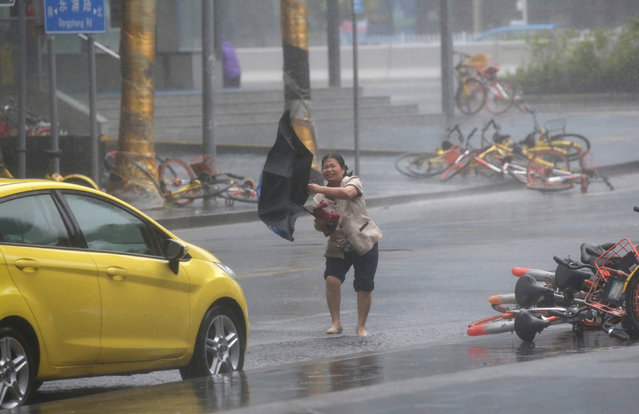 A woman holding an umbrella walks in the rainstorm as Typhoon Mangkhut approaches, in Shenzhen, China on September 16, 2018. (Photo by Jason Lee/Reuters)