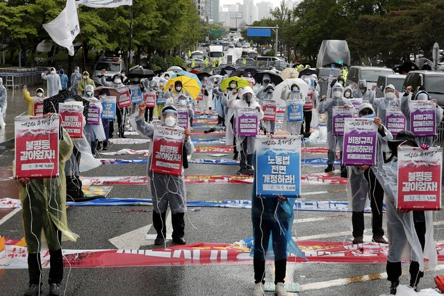 """Members of the Korean Confederation of Trade Unions stage a May Day rally demanding better working conditions and expanding labor rights in Seoul, South Korea, Saturday, May 1, 2021. The signs read: """"Let's solve inequality"""". (Photo by Ahn Young-joon/AP Photo)"""
