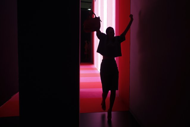 A model raises her arms as she walks backstage after presenting a creation from Agatha Ruiz de la Prada's Fall/Winter 2015 collection during the Mercedes-Benz Fashion Week in Madrid February 10, 2015. (Photo by Susana Vera/Reuters)