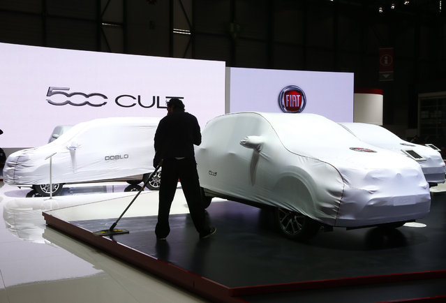 An employee cleans the FIAT booth ahead of the 85th International Motor Show in Geneva, March 2, 2015.       REUTERS/Arnd Wiegmann (SWITZERLAND  - Tags: TRANSPORT BUSINESS)
