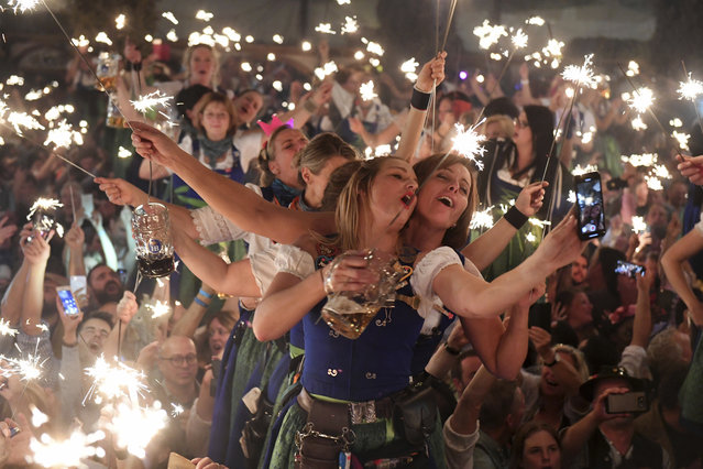 In this October 7, 2018 photo waitress dance in the Hofbraeu tent after the closing of the Oktoberfest beer festival in Munich, southern Germany, which ran from September 22 through October 7, 2018. (Photo by Felix Hoerhager/AP Photo)