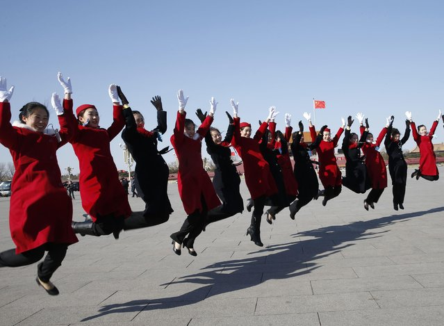 Hotel guides jump during the opening session of the Chinese People's Political Consultative Conference (CPPCC), at Tiananmen Square in Beijing March 3, 2015. REUTERS/Kim Kyung-Hoon