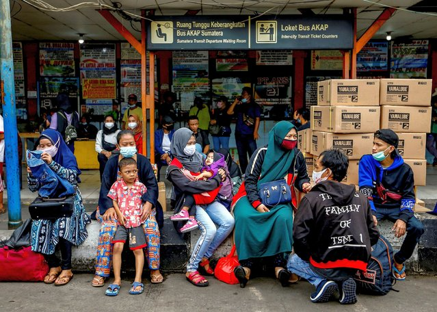 """Passengers wait for a bus to return to their hometowns, known locally as """"mudik"""", ahead of the Eid al-Fitr celebration, amid the coronavirus disease (COVID-19) outbreak, at Kalideres terminal, in Jakarta, Indonesia, May 3, 2021. (Photo by Ajeng Dinar Ulfiana/Reuters)"""