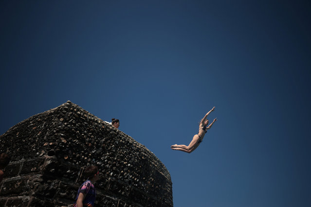 A person dives into the sea as people enjoy the hot weather on Brighton beach, in Brighton, Britain, June 1, 2021. (Photo by Hannah McKay/Reuters)
