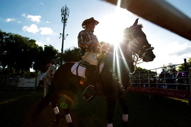 Horse rider prepares for a ride prior to a bull riding event in Santa Tecla, El Salvador, December 15, 2016. (Photo by Jose Cabezas/Reuters)