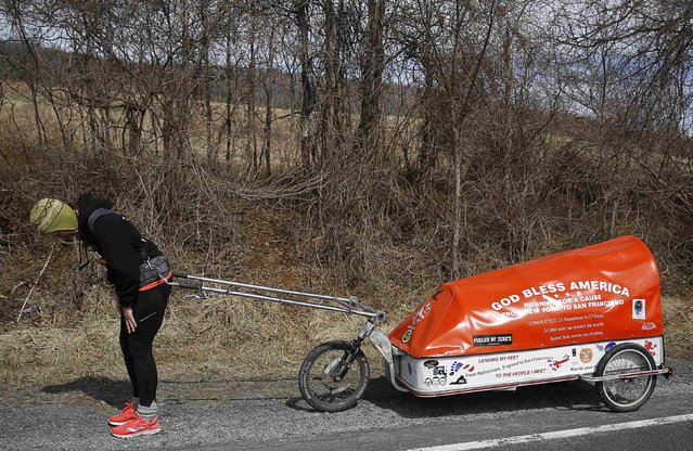 """Sixty-eight year old cross-country runner Rosie Swale-Pope rests after pulling her cart, """"The Icebird"""", in Upperville, Virginia March 13, 2015. (Photo by Gary Cameron/Reuters)"""