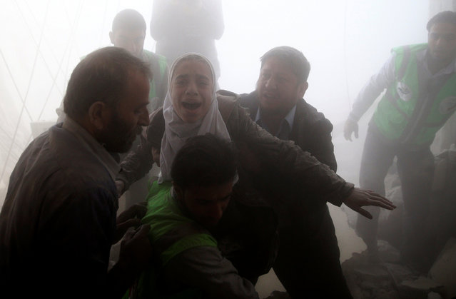 Men evacuate a girl from a site hit by an airstrike in the rebel-held Douma neighbourhood of Damascus, Syria November 7, 2016. (Photo by Bassam Khabieh/Reuters)
