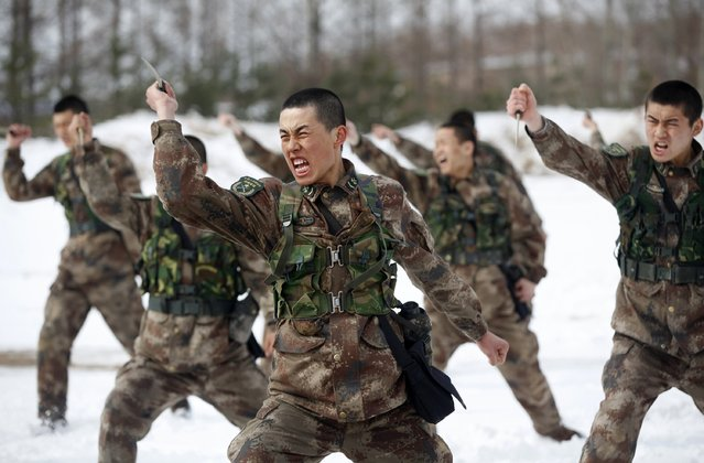People's Liberation Army (PLA) soldiers shout as they practise with knives during a training session on snow-covered ground at a military base in Heihe, Heilongjiang province March 18, 2015. (Photo by Reuters/China Daily)