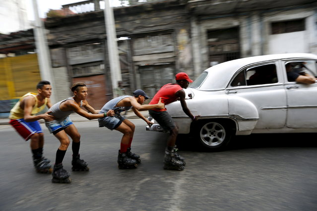 CUBA: Teenagers on roller skates hold on to each other as they are pulled by a vintage car to move along a street in Havana, Cuba March 19, 2016. (Photo by Ivan Alvarado/Reuters)