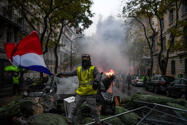 A demonstrator holds a french flag among christmas trees during a protest of Yellow vests (Gilets jaunes) against rising oil prices and living costs, on December 1, 2018 in Paris. Speaking at the Paris police's command centre, French Prime Minister said 36,000 people were protesting across France, including 5,500 in the capital for this 3rd nationwide day of blockade ands demos. (Photo by Alain Jocard/AFP Photo)