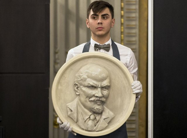 In this photo taken Wednesday, March 25, 2015, a clerk holds a depiction of Soviet revolutionary leader Lenin during an auction where people have spent euros 50,000 ($55,000 ) buying Communist memorabilia that included items belonging to the late Romanian dictator Nicolae Ceausescu in Bucharest, Romania. (Photo by Vadim Ghirda/AP Photo)
