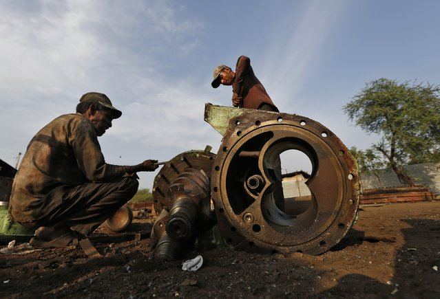 Workers dismantle the engine bearing of a decommissioned ship at the Alang shipyard in the western Indian state of Gujarat, March 27, 2015. (Photo by Amit Dave/Reuters)